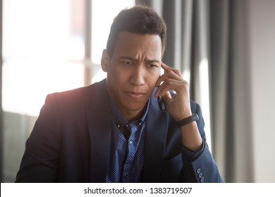 Concerned african American businessman talk over smartphone think of solving business problem, anxious stressed black male employee or boss have unpleasant cellphone conversation hearing bad news