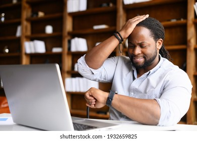Concerned African-American young man is late, check time on a wristwatch, a sadness guy forgot about an important meeting, worried male does not have time to finish the project before the deadline