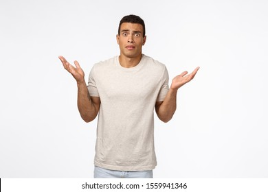 Concerned and alarmed tanned muscline young man standing shocked and confused, shrugging with hands spread sideways, stare camera anxious and indecisive, have trouble dont know how solve situation