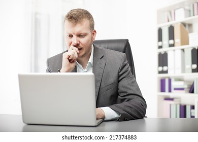 Concerned businessman working at his desk in the office staring at the screen of his laptop computer with a worried expression