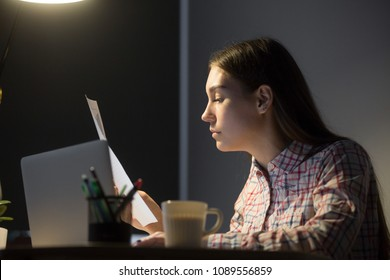 Concerned casual female worker reading printed handout paper, studying business information, analyzing company financial statistics, evaluating rates growing, corporate profit in home office at night