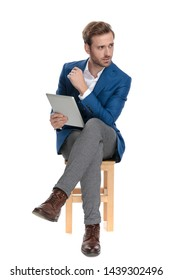 Concerned casual man holding his tablet and looking to the side while sitting with his legs crossed and wearing a suit on white studio background