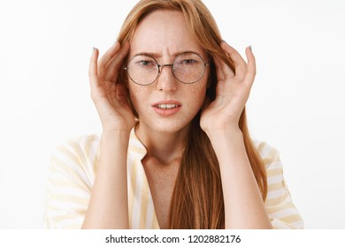 Concerned clueless and perplexed good-looking stylish female student in glasses frowning and squinting holding hands on temples of head being troubled or suffering headache over white wall