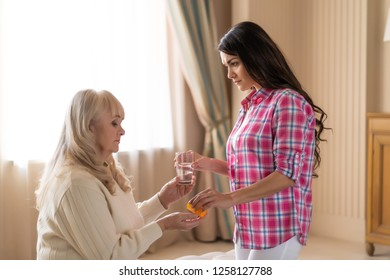 Concerned Daughter Gives Her Mother Who Is Feeling Unwell A Glass Of Water And Prescribed Medication.
