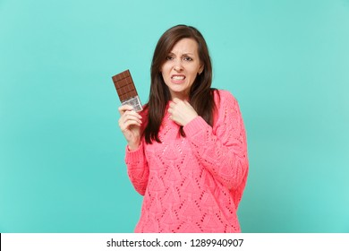 Concerned dissatisfied young woman in knitted pink sweater holding in hand chocolate bar isolated on blue turquoise wall background, studio portrait. People lifestyle concept. Mock up copy space