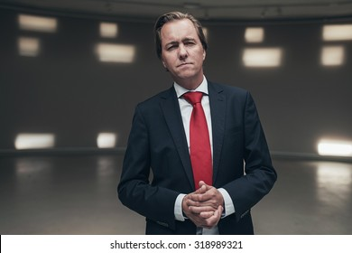Concerned entrepreneur wearing suit with red tie standing in empty room.