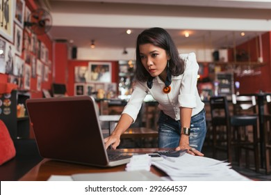 Concerned female bar owner looking at laptop screen