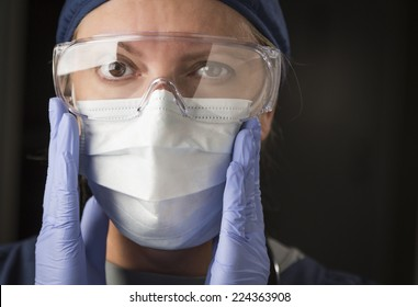 Concerned Female Doctor or Nurse Putting on Protective Facial Wear.