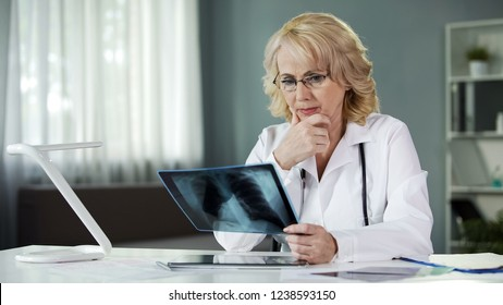 Concerned female pulmonologist examining X-ray of patient's lungs, diagnostics