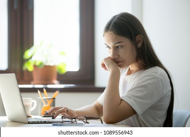 Concerned female worker looking at laptop screen suspiciously, thinking about problem solution, reading ambiguous email or negative news. Concept of focus and concentration