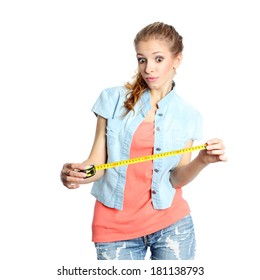 Concerned girl looks down at tape measure.