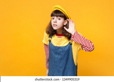Concerned girl teenager in french beret and denim sundress eavesdrop with hearing gesture isolated on yellow wall background in studio. People sincere emotions, lifestyle concept. Mock up copy space