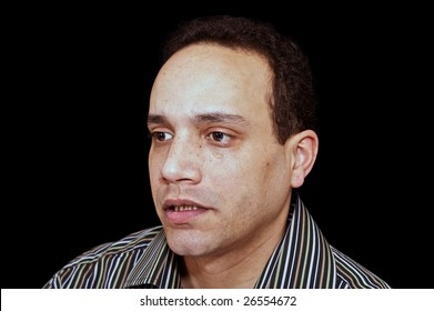 concerned looking portrait of african american male wearing striped shirt against black background
