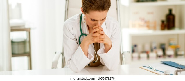 Concerned medical doctor woman sitting in office