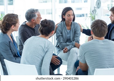 Concerned men comforting another in rehab group at a therapy session