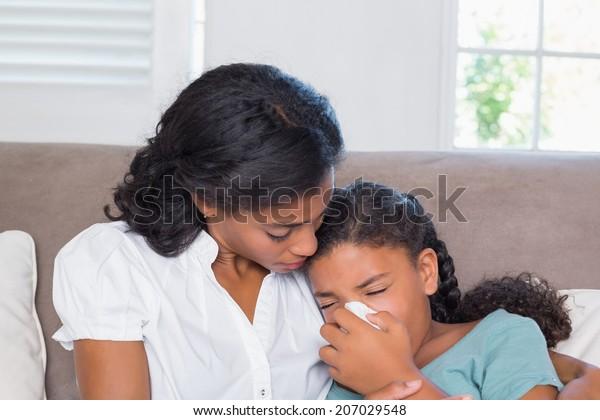 Concerned mother cuddling sick daughter at home in living room
