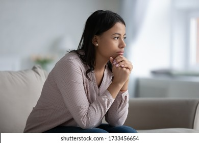 Concerned sad African woman sit on sofa in living room thinking of problem looks in distance feels depressed due loneliness, inner emptiness, life troubles, break up or divorce, marriage split concept