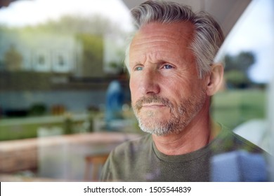 Concerned Senior Man Standing And Looking Out Of Kitchen Door Viewed Through Window