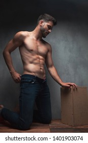 Concerned sexy man adjusting his jeans and kneeing while leaning on a box and looking sideways on gray studio background