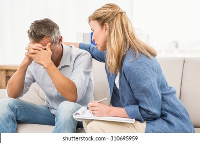 Concerned therapist comforting male patient in the office