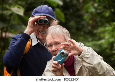 Concerned woman with camera and happy man with binoculars