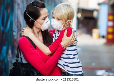 A concerned woman looking at her sick son. Both are wearing protective face masks for pollution or virus.