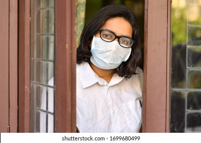 Concerned & worried lady under lock down home quarantine wearing protective breathing surgical face mask against flu and novel Corona virus (Covid-19) pandemic & greeting visitor through door/window