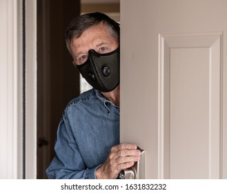 Concerned and worried man wearing a protective breathing mask against flu and coronavirus and greeting visitor