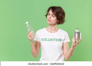 Concerned young brunette woman in volunteer t-shirt isolated on pastel green background. Voluntary free work assistance help charity grace teamwork concept. Hold trash empty plastic bottle, tincan