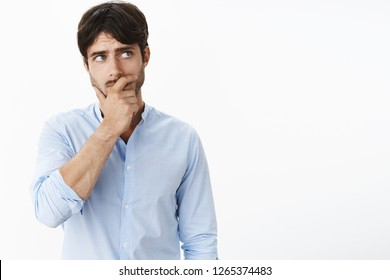 Concerned young good-looking mature husband with blue eyes and bristle holding hand on jaw, frowning and looking at upper right corner as thinking, being troubled and uneasy, posing over white wall