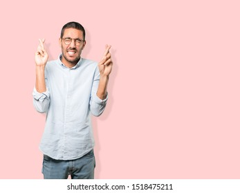 Concerned young man doing a crossed fingers gesture