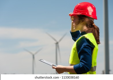 Concert of alternative energy and technology of the future. Side view cute young woman engineer in red helmet and green vest with work plan and smartphone in hands looking somewhere into the distance