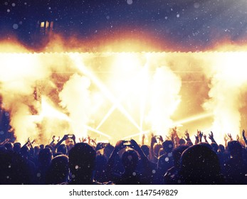 Concert audience under a rain of dust particles and confetti, stage is visible ahead