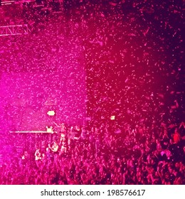 A concert with confetti falling from the ceiling shot with a bright instagram filter for a modern look.