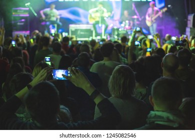 Concert crowd with arms raised, silhouettes of people with smartphones.