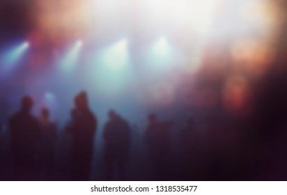 Concert crowd background.Blurred backdrop of musical festival audience on dance floor in bright stage lights in nightclub.Club concerts back ground with bokeh lights effect.Blue and yellow lights