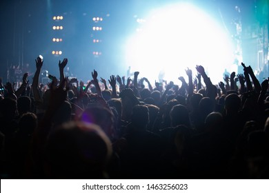 Concert crowd of excited music fans waving hands on dance floor in nightclub.Youth entertainment event background.Happy people partying on dance floor.Curated concerts photos and images collection