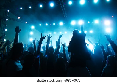 Concert crowd in front of bright stage lights. Silhouettes of people.