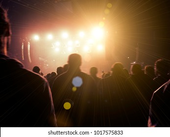 Concert crowd in front of a warmly lit stage