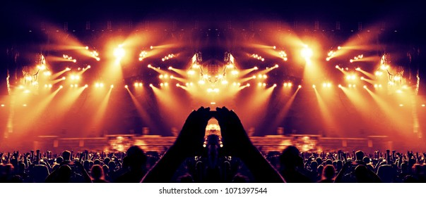 Concert crowd in a huge arena with a brightly lit stage