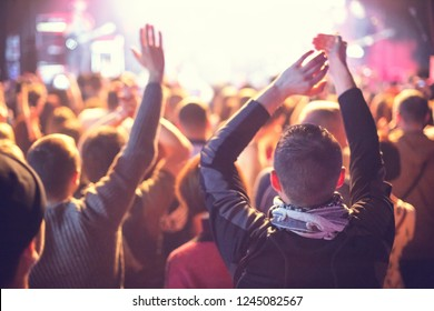 A concert crowd of people applauds the artist.
