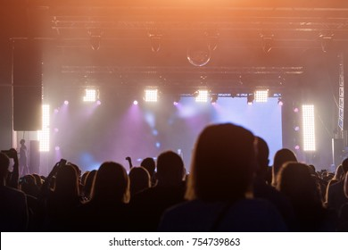 Concert Crowd. People silhouettes in front of bright stage lights. Band of rock stars