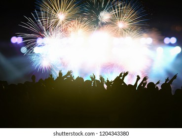 Concert crowd in silhouettes of Music fanclub with show hand action for celebrate with fireworks, happy new year and christmas concept