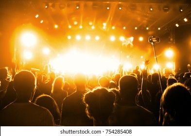 Concert Crowd. Silhouettes young people in front of bright stage lights. Band of rock stars