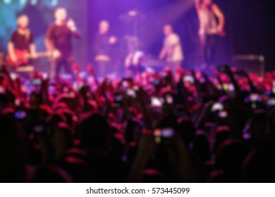 Concert crowd.Background of crowded dance floor in nightclub.Live music show in night club.People have fun on rock concerts.Blurred group of young people on gig