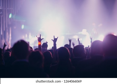 Concert, event or party concept. People with hands up at the scene, spotlight, colored light.