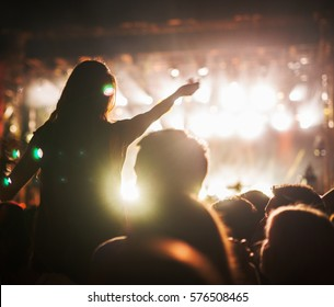Concert girl at crowd on music festival.