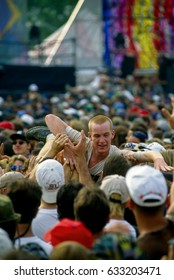 "Concert goers crowd surf in the mosh pit in front of the main stage as the  ""Blues Traveler"" rock band performs on stage Saugerties, New York, August 12, 1994."