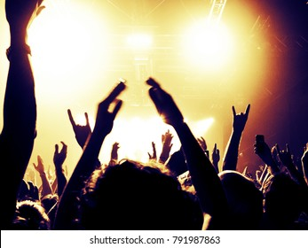 Concert hall with crowd clapping in front of the stage