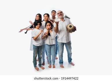 Concert of Indian family of six playing music instruments in a group and senior lady singing, standing against white background
